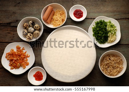 Vietnamese street food, baked girdle cake, a famous snack food make from rice paper, onion, shrimp, sausage, quail egg, chili sauce, people also call this eating is Vietnam pizza