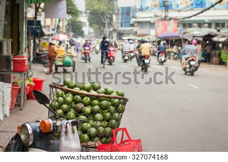 Vietnamese street hawker with a basket full of sweet oranges on bike in Ho Chi Minh city. - stock photo