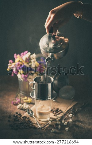 Vietnamese style drip coffee, Woman hand pouring hot water into metal coffee filter with film filter effect - stock photo