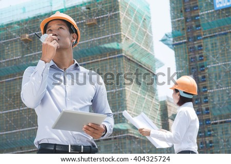 Vietnamese supervisor with digital tablet using walkie-talkie at construction site - stock photo