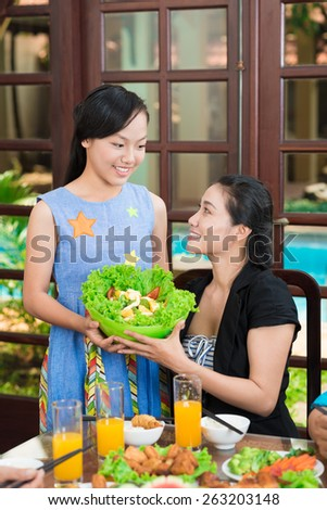 Vietnamese teenage girl giving her mother a bowl of salad - stock photo