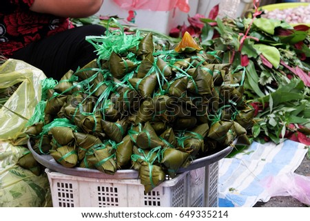 Vietnamese traditional food for may 5th, is double five festival or tet doan ngo, group of sticky rice cake in green leaf, also call banh u tro with pyramidal shape at open air market