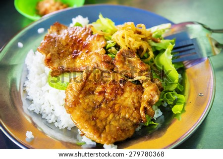 Vietnamese Traditional Food: Steamed rice with fried pork rib and veggies in disposable plastic takeaway boxes. - stock photo