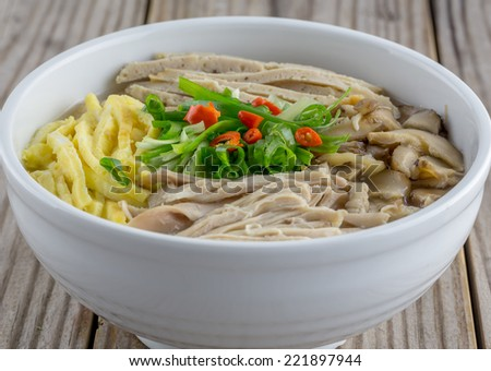 Vietnamese vermicelli with egg, pork, chicken and shiitake mushroom in a hot broth. - stock photo