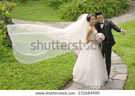 Vietnamese wedding couple in the park, groom showing something to his bride - stock photo