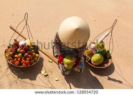 Vietnamese woman in a straw hat on the beach selling fruit and reveals the coconut