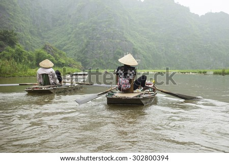 Vietnamese woman in traditional conical hat rows boat into natural cave on Ngo Dong river, Tam Coc, Ninh Binh, Vietnam