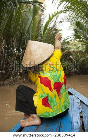 Vietnamese woman rows a boat in Mekong River in Vietnam - stock photo