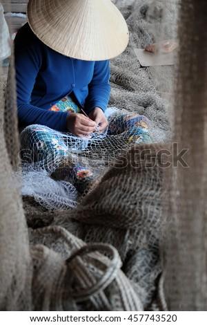 Vietnamese woman sewing fishing net at Ca Mau,Vietnam