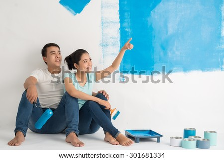 Vietnamese young couple taking break from painting the wall in new apartment - stock photo