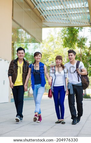Vietnamese young couples walking down the street - stock photo