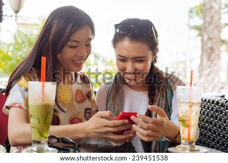 Vietnamese young girls sitting in the cafe and watching something on the smartphone - stock photo