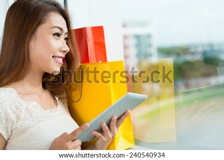 Vietnamese young lady shopping online via digital tablet - stock photo