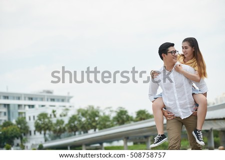 Vietnamese young man giving piggyback ride to his girlfriend
