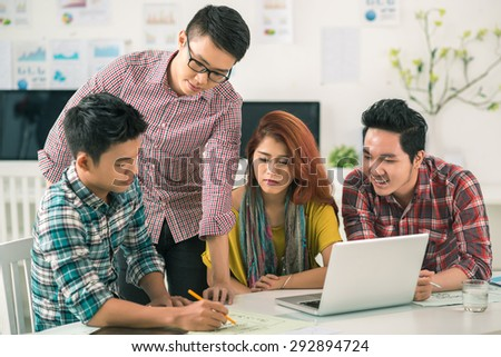Vietnamese young man sharing his ideas with colleagues