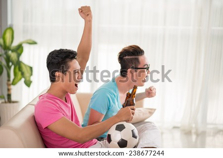 Vietnamese young men sitting on the sofa and supporting favorite soccer team - stock photo
