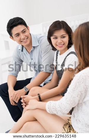 Vietnamese young people chatting indoors - stock photo