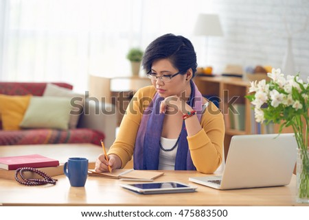 Vietnamese young woman writing her ideas in notepad