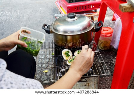 Vietnmese people cooking shell for sale on street at Saigon city in Ho Chi Minh, Vietnam - stock photo