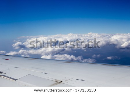 View above the clouds from a modern  passenger jet  plane at a height of 10 kilometers  flying over  arid iron ore country of  Pilbara in Western Australia on a hazy smoke filled afternoon in summer. - stock photo