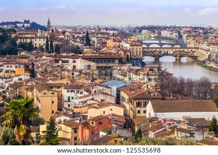 View above the roofs of Florence with river Arno and Ponte Vecchio on the right side. - stock photo