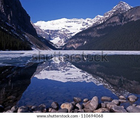 View across a part frozen Lake Louise, Banff National Park, Alberta, Canada. - stock photo