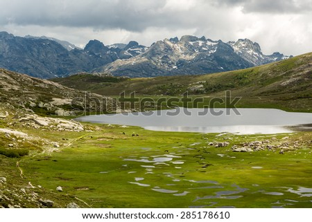 View across Lac De Nino in Corsica with a stream meandering across a green plain in foreground and  dark clouds and snow capped mountains in the background