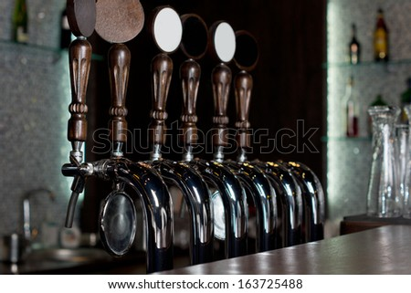 View across the counter of a row of beer taps on a stainless steel mechanical keg in a pub used to dispense draught beer