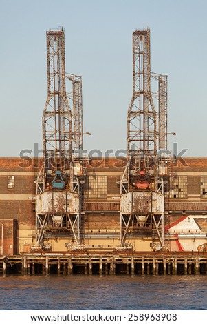 View across the Hudson River to an old wharf and cargo gantry New York city - stock photo