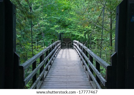 View across uspended footbridge across Presque Isle River at Porcupine Mountain State Park on the Upper Peninsula of Michigan. - stock photo