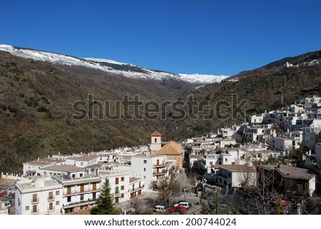 View across white village towards the snow capped mountains of the Sierra Nevada, Pampaneira, Las Alpujarras, Granada Province, Andalusia, Spain, Western Europe. - stock photo