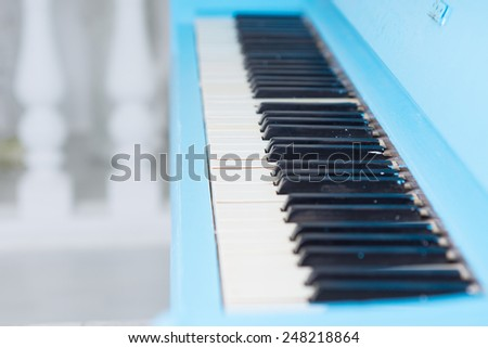 View along a blue piano keyboard with the lid open to display the ivories of the keys conceptual of entertainment and a classical performance - stock photo