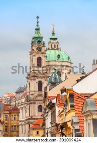 View along Mostecka street of St Nicholas Church in Prague - stock photo