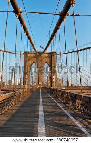 View along the pedestrian walkway, Brooklyn Bridge towards Manhattan, New York through the steel suspension cables and tower in warm light
