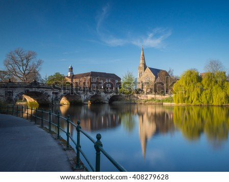 View along the river Severn to the English Bridge, Shrewsbury and a church and prominent willow tree, England, UK. - stock photo