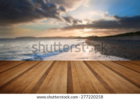 View along West coast of Wales towards beautiful sunset with sunbeams and stunning clouds formations with wooden planks floor - stock photo