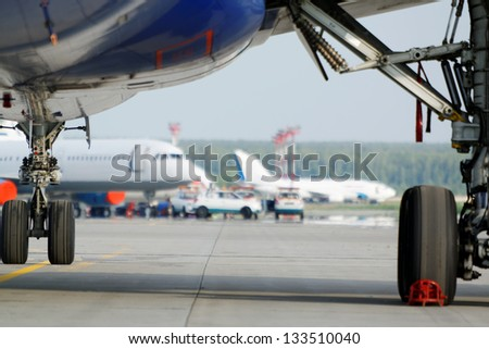 View at airfield from under wing of plane standing on parking - stock photo