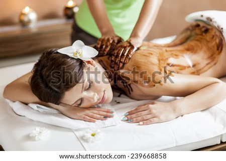 View at the back of the woman having a hot chocolate massage - stock photo