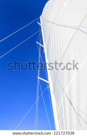 View at the bottom looking up at boat mast with rigging and blue sky - stock photo