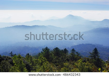 View Beautiful Mountain mist.smoky mountains hazy blue skies and the smoke or fog line.Doi Inthanon national park, ChiangMai, Thailand.selective focus.soft focus the field for background.
