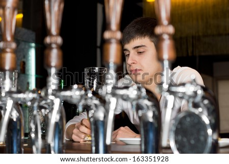 View between the stainless steel beer taps behind the counter of a young man seated alone at a bar drinking