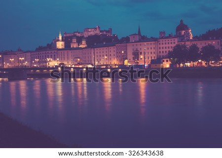 View city, far hills, mountains. Blue, purple night sky. Walk evening on curve river. Vintage photo. Poster, Bokeh background, Salzburg, Austria, Europe. evening lights city. Spain, France, Italy