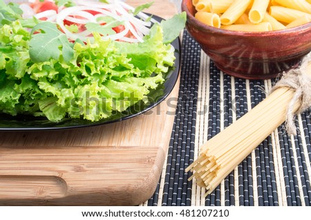 View close-up on food composition of fresh salad on a plate, and pasta in a wooden bowl and a serving of spaghetti cooking