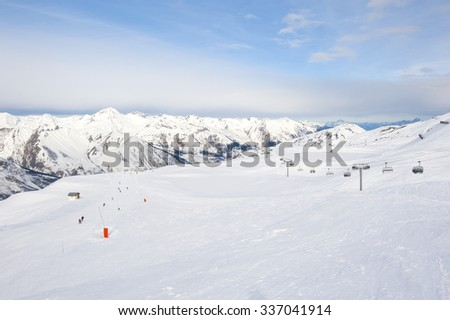 View down a snowy ski piste in alpine mountain valley - stock photo