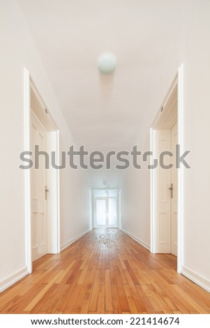 View down a straight receding long white interior passage with wooden parquet floor and two opposing doors leading off it - stock photo
