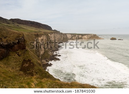 View down cliffs and coastline by Carrick a Rede suspension bridge to Carrick Island in Northern Ireland - stock photo