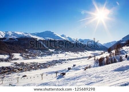 View down on typical Alpine ski resort and ski slopes, Livigno, Italy, Europe - stock photo