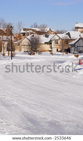 View down snowy winding street in Minnesota neighborhood - stock photo