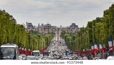 View down the Champs Elysees towards the Grand palace with traffic and heat haze - stock photo