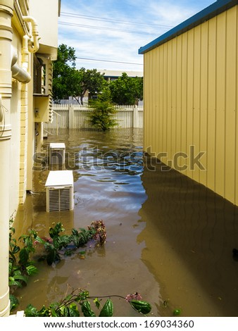 View down the side of a house during Brisbane floods.  Air-conditioning units and garage are in water - stock photo